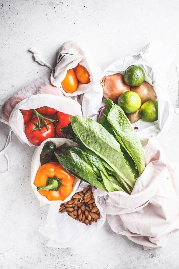 在eco棉花袋子,胡椒,蕃茄,莴苣,黄瓜,石灰,葱的菜 零的浪费的食物购物 库存图片
