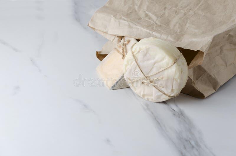 在eco纸和普罗卧干酪包装的荷兰扁圆形干酪,在白色大理石桌上的纸袋 免版税库存图片