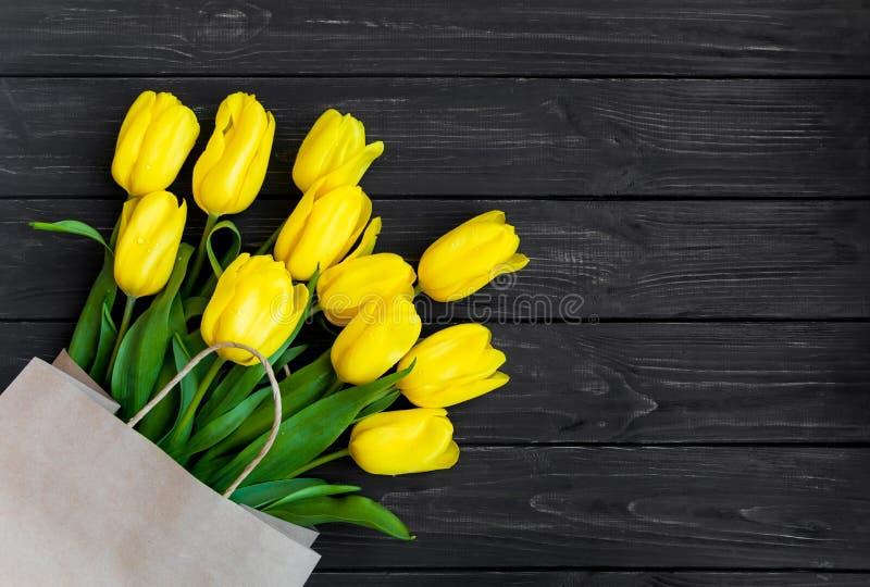 在eco纸袋的明亮的黄色郁金香在黑葡萄酒木桌上 平的位置,顶视图 库存照片