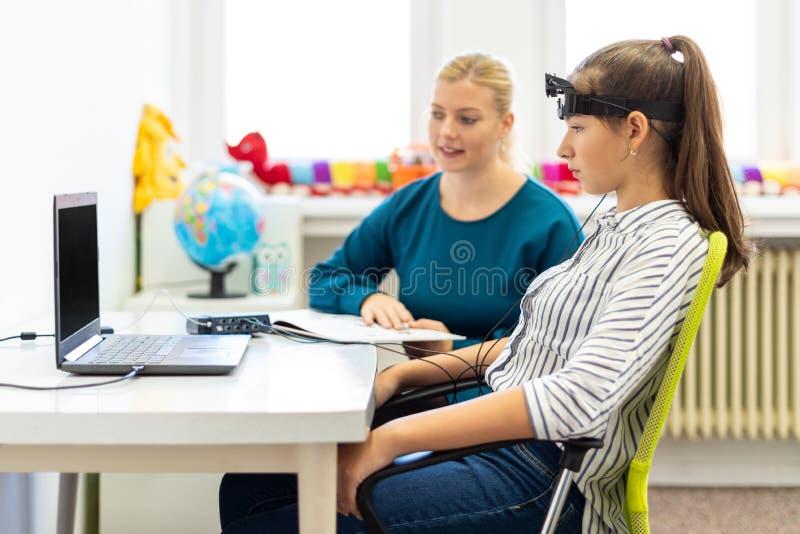 在EEG neurofeedback会议期间的年轻十几岁的女孩和儿童治疗师 脑波记录仪概念 图库摄影