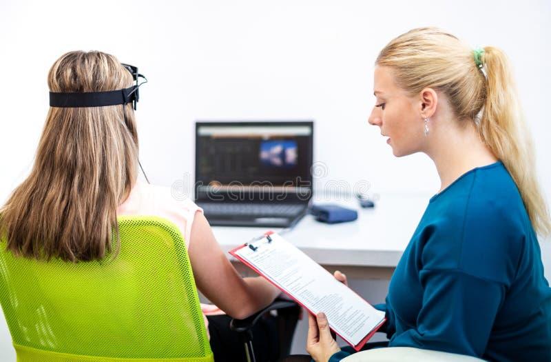 在EEG neurofeedback会议期间的年轻十几岁的女孩和儿童治疗师 脑波记录仪概念 库存图片