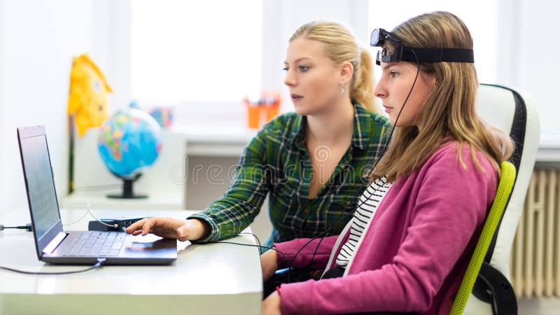 在EEG neurofeedback会议期间的年轻十几岁的女孩和儿童治疗师 脑波记录仪概念 免版税库存照片