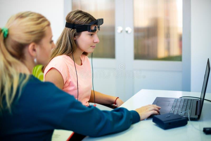 在EEG neurofeedback会议期间的年轻十几岁的女孩和儿童治疗师 脑波记录仪概念 免版税库存图片