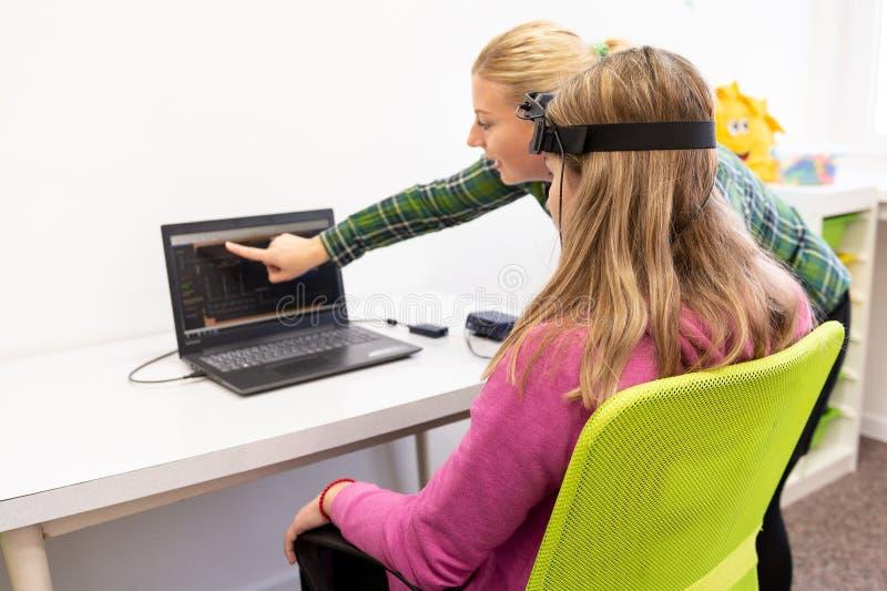在EEG neurofeedback会议期间的年轻十几岁的女孩和儿童治疗师 脑波记录仪概念 库存照片