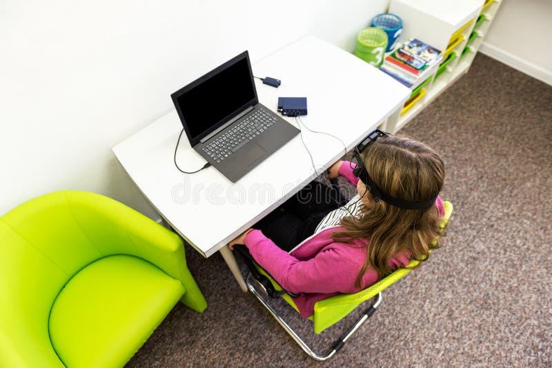 在EEG neurofeedback会议期间的年轻十几岁的女孩 脑波记录仪概念 顶视图 免版税库存照片