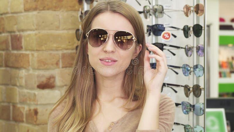 在eyewear商店的惊人的少妇微笑的尝试的太阳镜 免版税库存照片