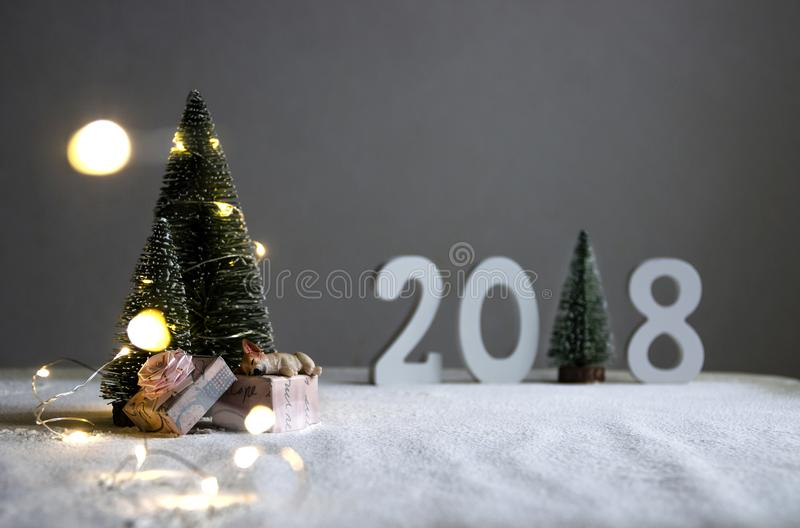 在fieldthe狗在礼物睡觉,并且在距离图2018年在一棵圣诞树的角色与光的地方 库存图片