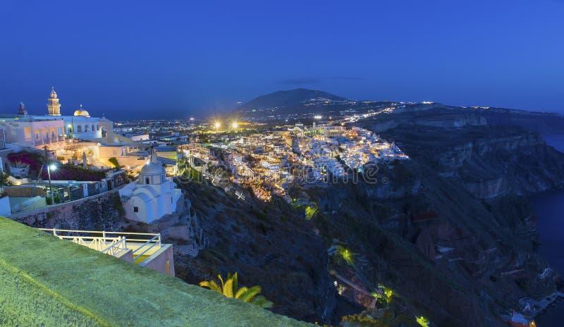 在Fira镇的美丽如画的空中全景和周边地区在晚上 圣托里尼(锡拉)海岛 库存图片