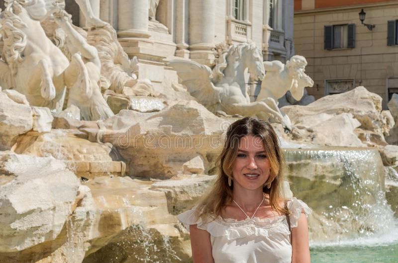 在Fountain de Trevi附近的年轻俏丽的女孩在罗马,意大利 免版税库存图片