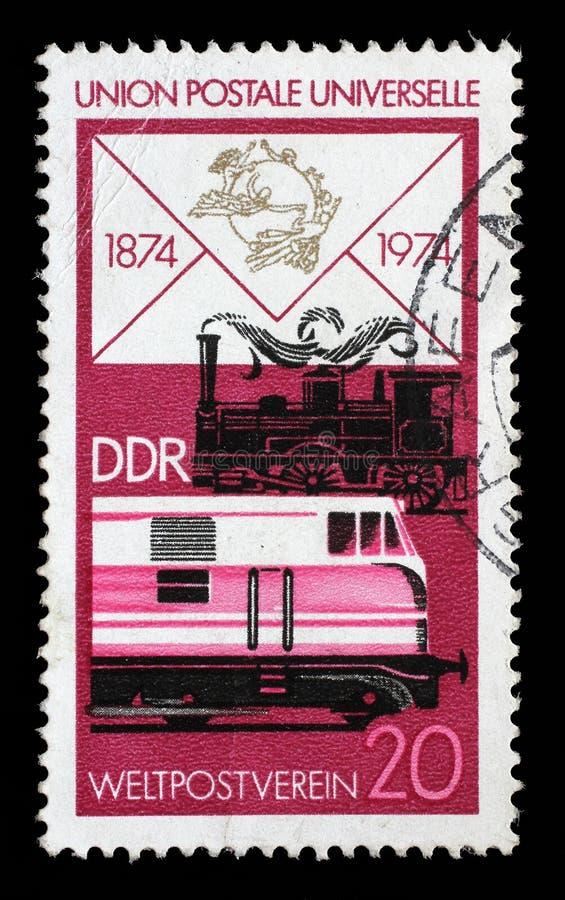 在GDR打印的邮票显示老蒸汽机车和现代柴油 免版税库存图片