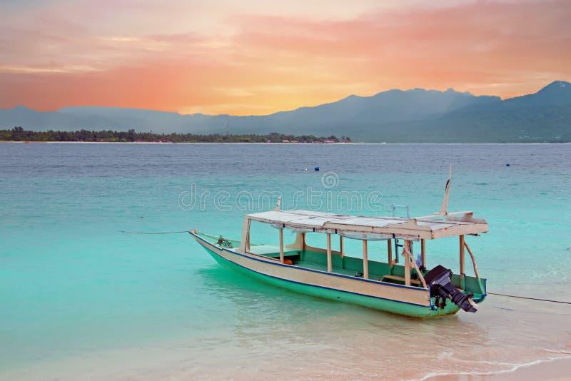 在Gili Meno海岛海滩,日落的印度尼西亚的传统小船 图库摄影