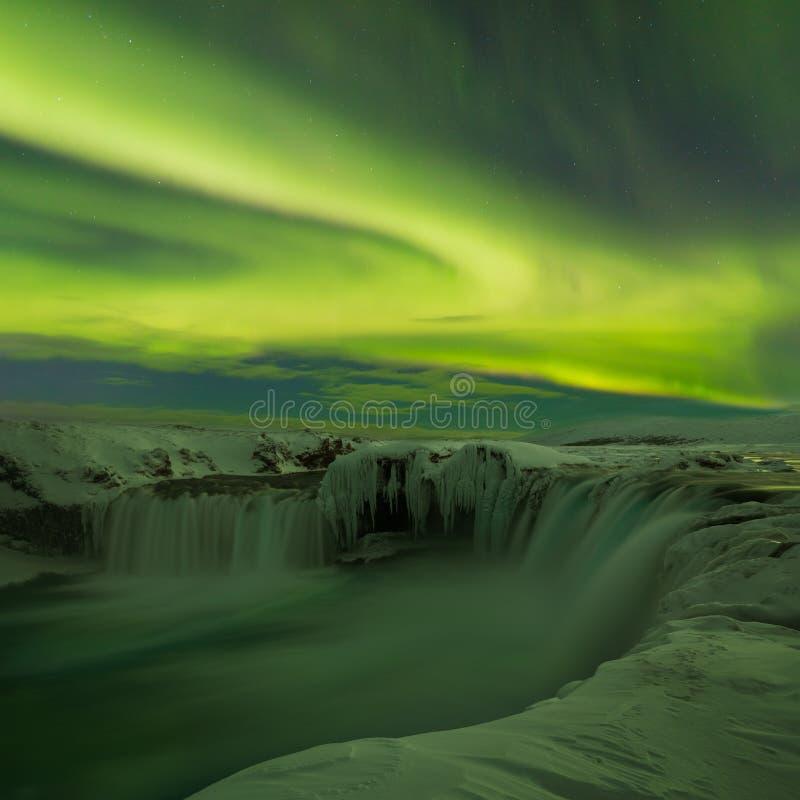 在Godafoss瀑布上风景的惊人的极光在冬天冰岛 绿色北极光 与极光的满天星斗的天空 库存图片