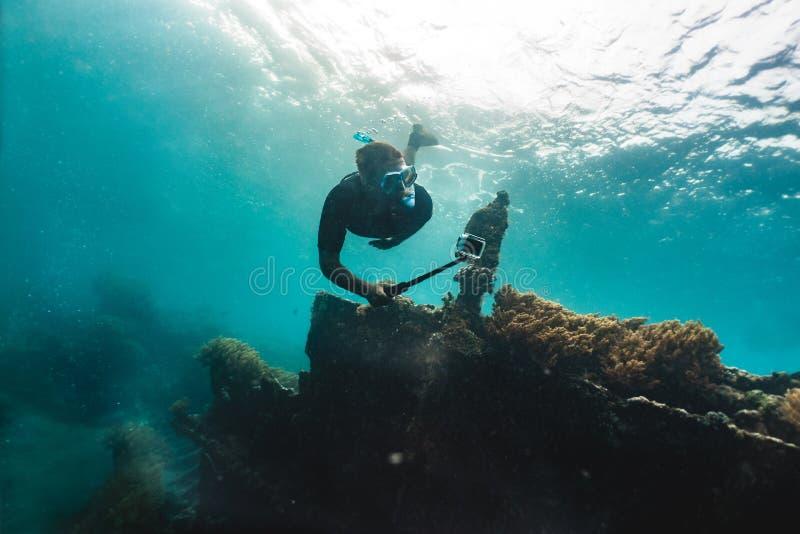 在gopro珊瑚礁的Freediver射击与在wreckship附近的鱼 图库摄影