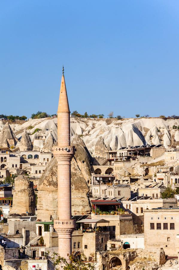 在Goreme,在凝灰岩雕刻的山风景使火山岩形成的镇,石房子陷下卡帕多细亚,土耳其 免版税库存照片