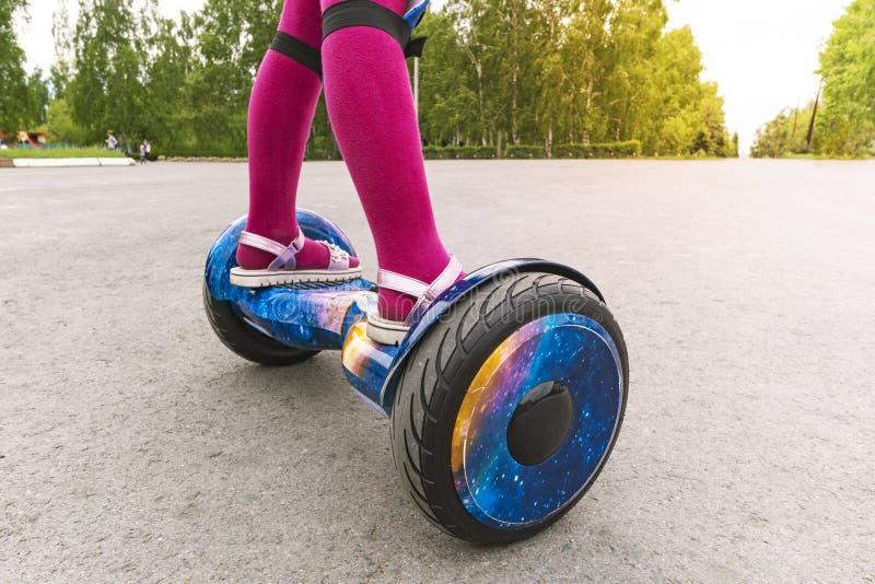在gyroscooter的女孩乘驾 一女孩的脚桃红色裤袜和凉鞋的是在GyroScooter 免版税库存图片