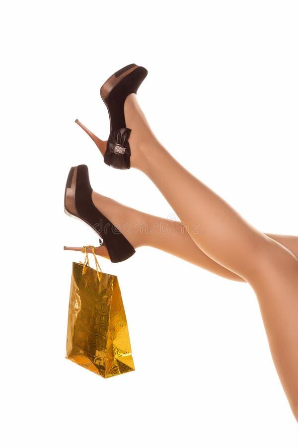 在highheels的亭亭玉立的长的性感的妇女腿与购物袋。购物concep 免版税图库摄影