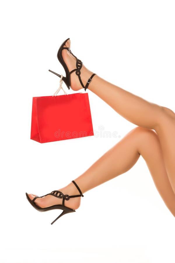 在highheels的亭亭玉立的长的性感的妇女腿与购物袋。购物concep 库存图片