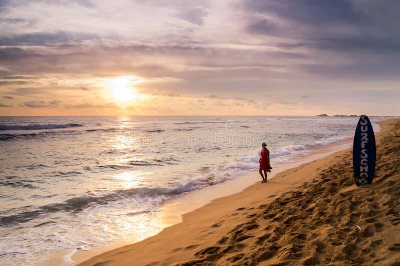 在Hikkaduwa海滩的日落,与红色的一个夫人 库存照片
