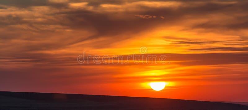 在hillls的最低纲领派多云五颜六色的日落, 免版税库存图片