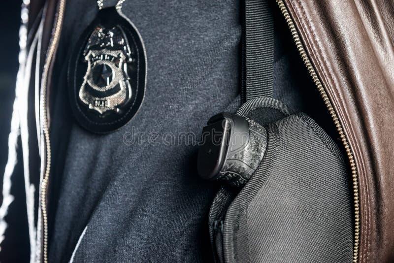 在holst的警察和枪的特写镜头中央部位有徽章的 免版税库存图片