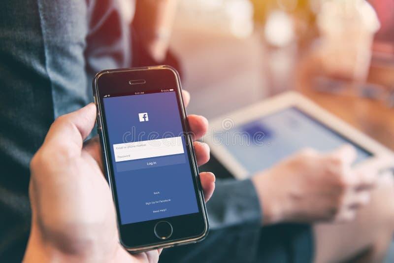 在iPhone的Facebook App与使用在智能手机的人片剂背景特写镜头男性手举行社会网络 图库摄影