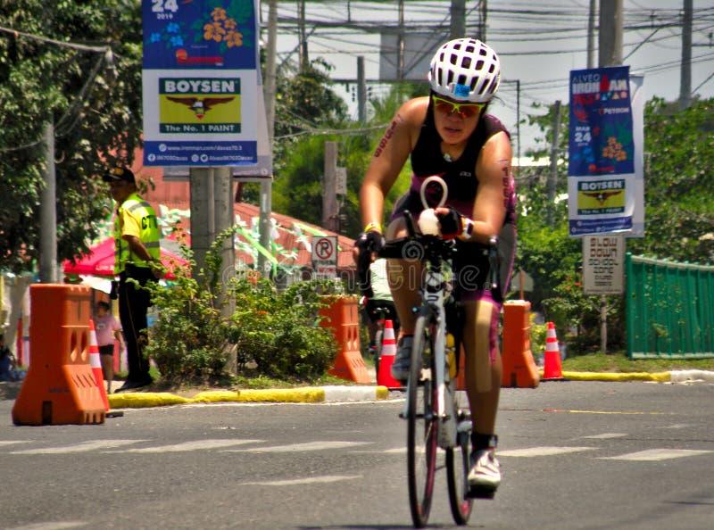 在Ironman期间的一个妇女骑自行车者2019体育比赛恶劣环境测井在达沃,菲律宾 库存照片