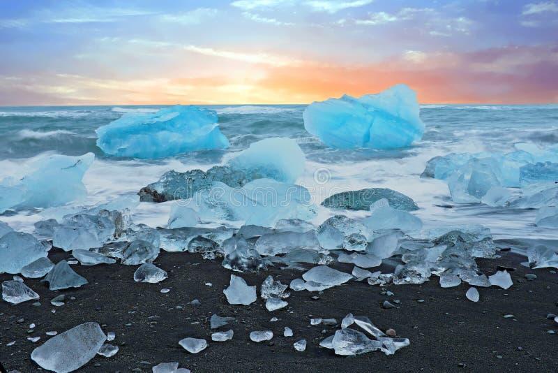 在Jokulsarlon冰在一个黑沙子海滩的岩石在冰岛在微明 库存照片