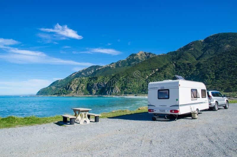 在Kaikoura海滩,新西兰的拖车有蓬卡车 库存照片