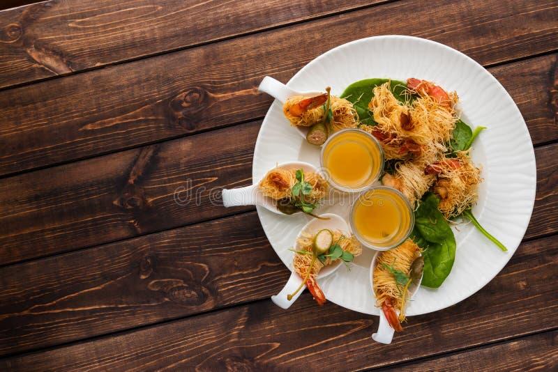 在Kataifi外壳的酥脆虾和麝香草用在玻璃的香宾调味汁在木质的背景的一块白色板材说谎 ?? 免版税库存照片