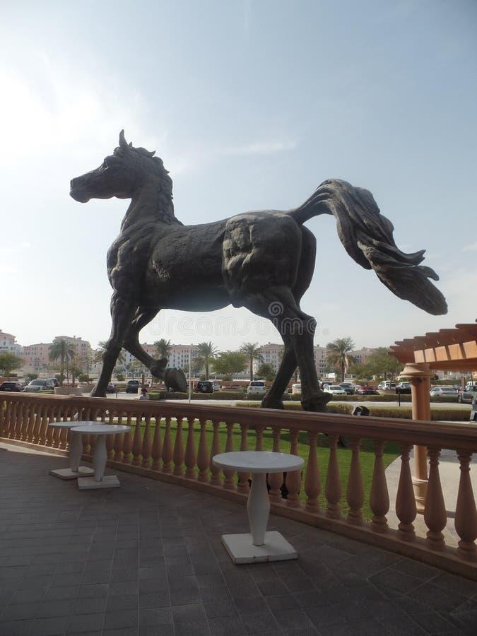 在Kempinski Marsa Malaz之外的巨型马雕塑在卡塔尔 免版税库存照片