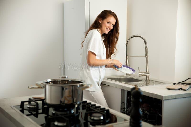 在kictchen的美丽的少妇洗涤盘 库存照片