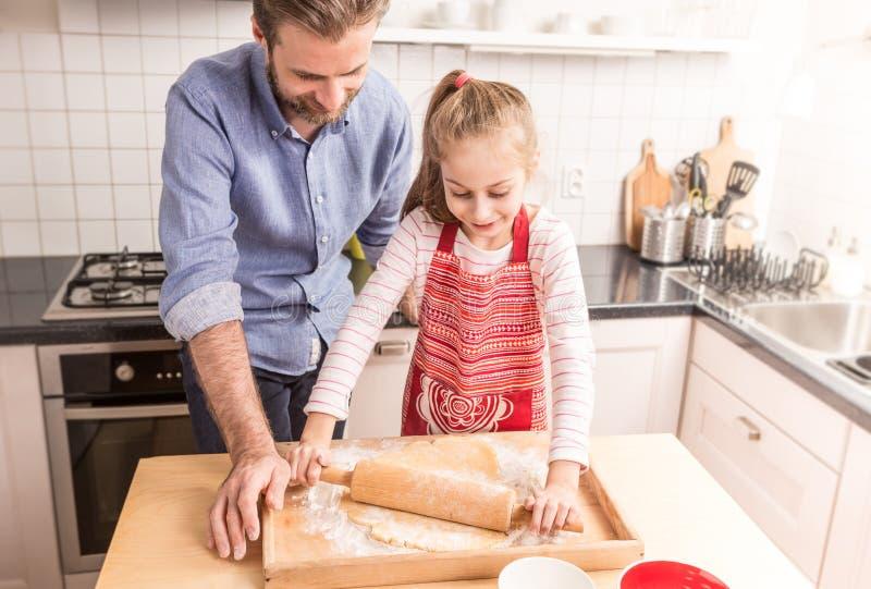 在kitche的愉快的父亲和女儿铺开的曲奇饼面团 免版税库存照片