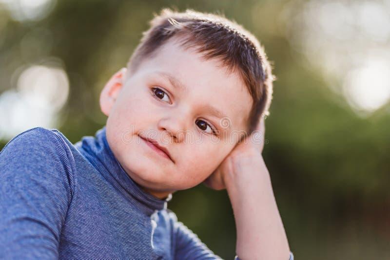 在kontrovoy日落光的布朗目的逗人喜爱的五岁的男孩关闭 在被弄脏的背景的儿童的面孔 免版税图库摄影