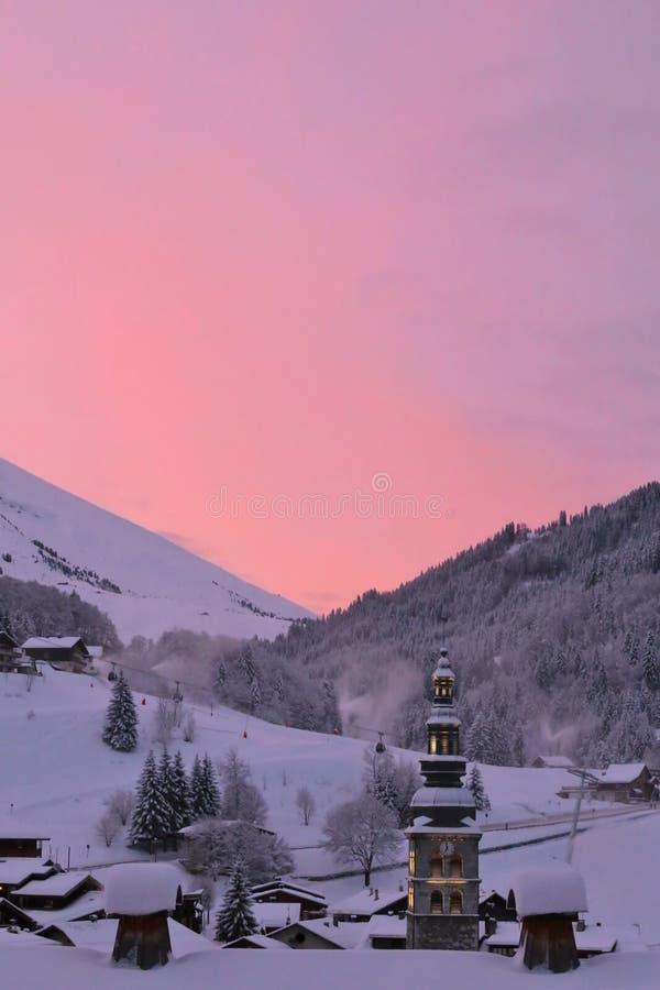 在La CLusaz的日出,在法国阿尔卑斯,有在村庄中间的教会的 免版税图库摄影