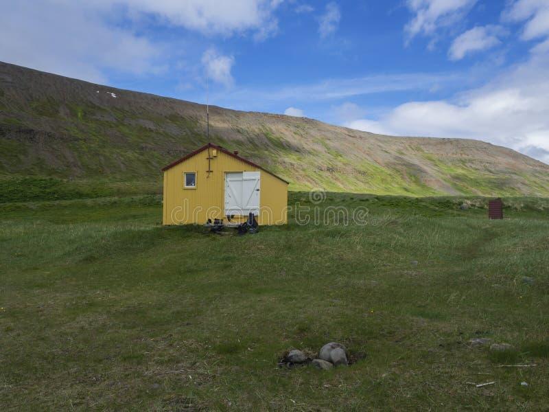 在latrar露营地的看法与黄色紧急风雨棚客舱的adalvik小海湾的在西部海湾Hornstrandir在冰岛 库存图片