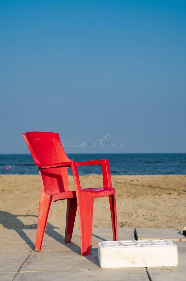 在Lido di斯皮纳,意大利海滩的空的红色塑料椅子  图库摄影