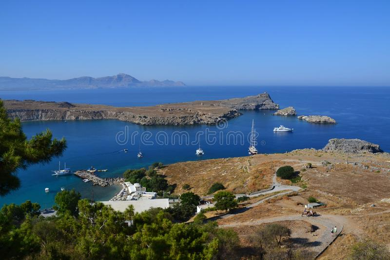 在Lindos、罗得岛、希腊、蓝天、橄榄树和美好的海视图上城的希腊文化的stoa的专栏在后面 免版税库存照片