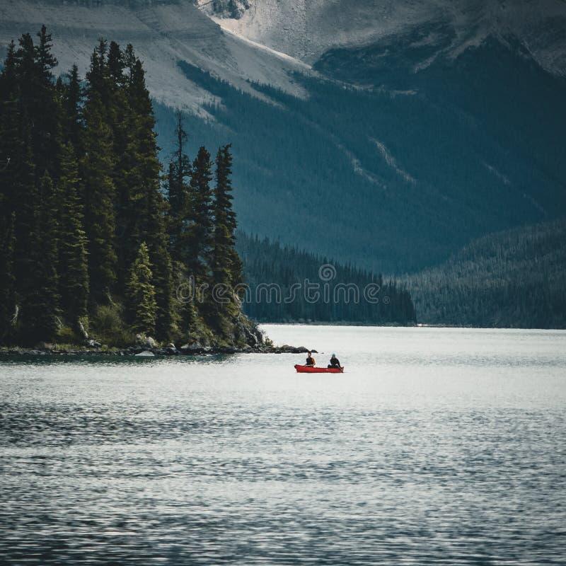 在maligne湖的一个独木舟在与加拿大罗基斯的背景的夏天在贾斯珀国家公园,亚伯大,加拿大 免版税库存照片