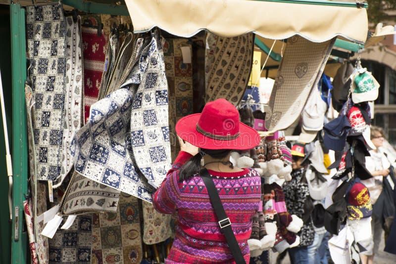 在Maran市的旅客亚裔泰国妇女选择和购物的织品在梅拉诺,意大利 免版税库存照片