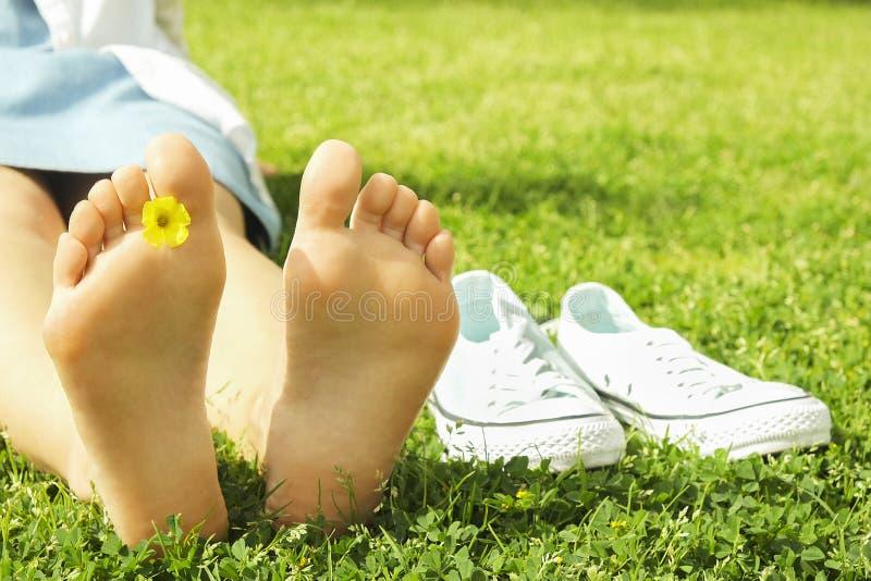 在mawed草坪草的女性赤脚 赤足休息的少妇户外,采取断裂概念 学院校园围场的学生 图库摄影