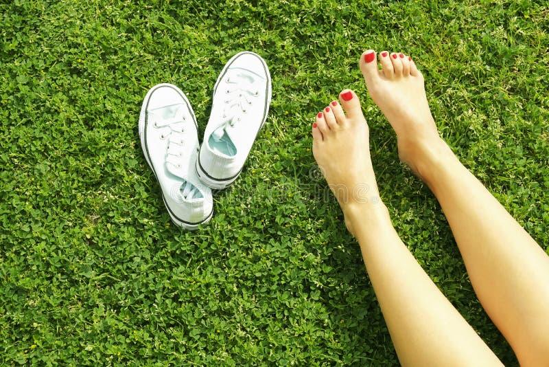 在mawed草坪草的女性赤脚 赤足休息的少妇户外,采取断裂概念 学院校园围场的学生 库存图片