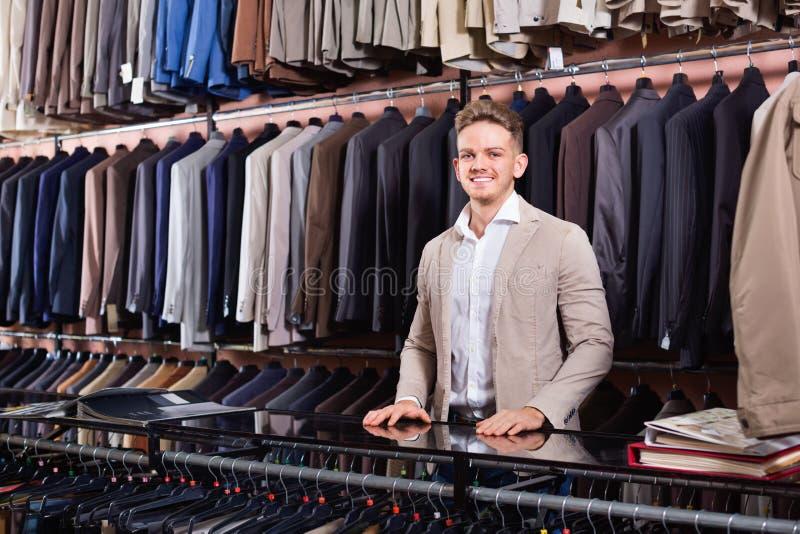 在men's布料商店供以人员显示不同的衣服的卖主 库存照片