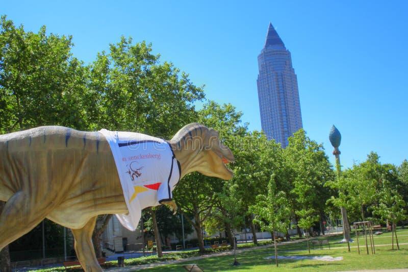在Messeturm和Senckenberg博物馆之间的公园 恐龙穿德国国家队的球衣 免版税库存照片