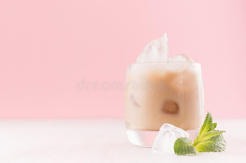 在misted玻璃的乳脂状的冷的新鲜的饮料与冰块、绿色薄菏和镶边秸杆在现代浅粉红色的内部,拷贝空间 免版税库存照片