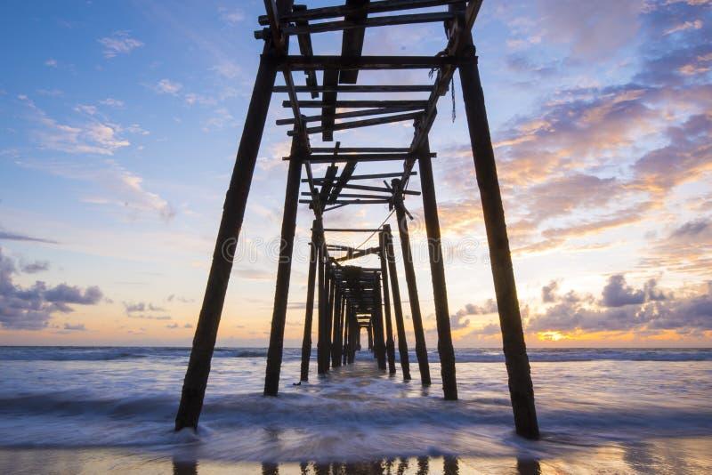 在Natai海滩的老木桥与在微明的美丽的天空 免版税库存照片