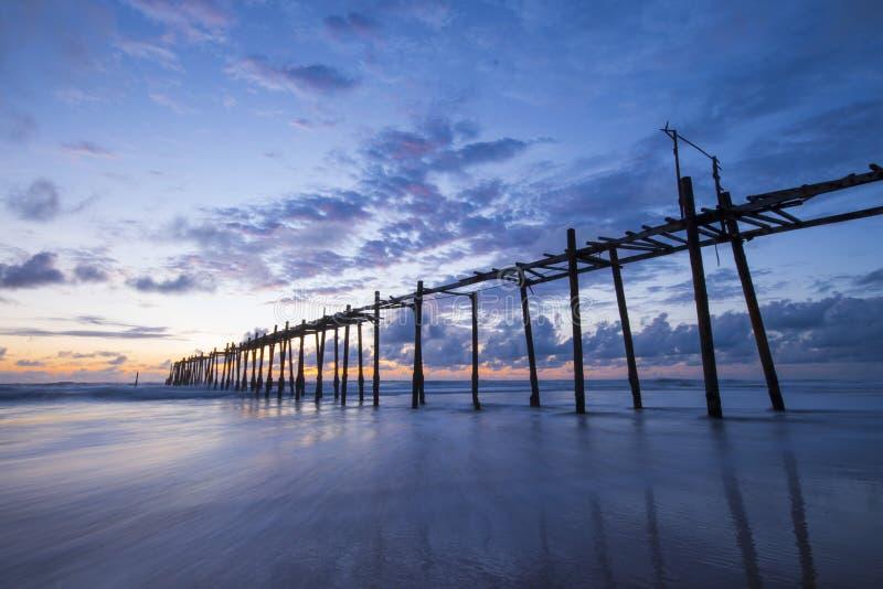 在Natai海滩的老木桥与在微明的美丽的天空 免版税图库摄影