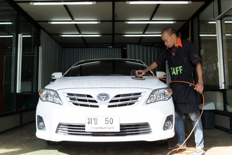在Nong洗车,曼谷泰国-在汽车的商标丰田,在洗车的职员工作者手擦亮的洗车 库存照片