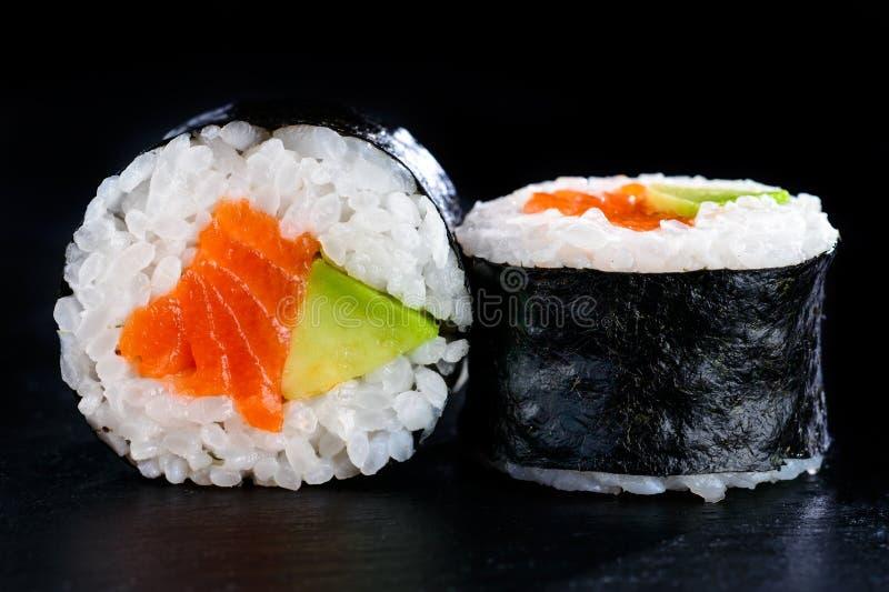 在nori的鲜美寿司卷用鲕梨和红色鱼在黑暗后面 免版税库存照片
