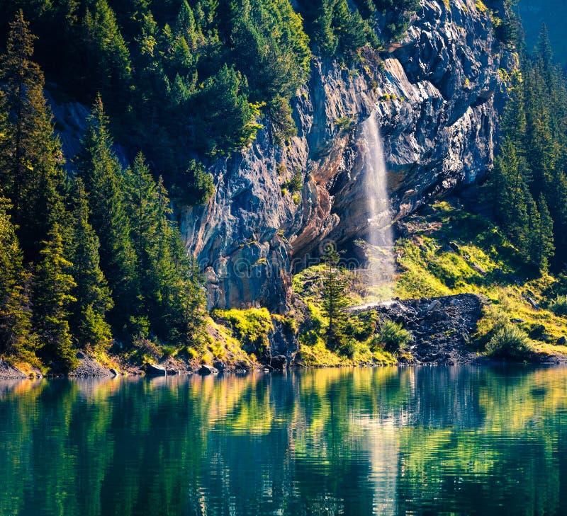 在Oeschinensee湖的闪耀的瀑布 精采夏天早晨在瑞士阿尔卑斯山脉,坎德斯泰格村庄地点,瑞士, 库存图片