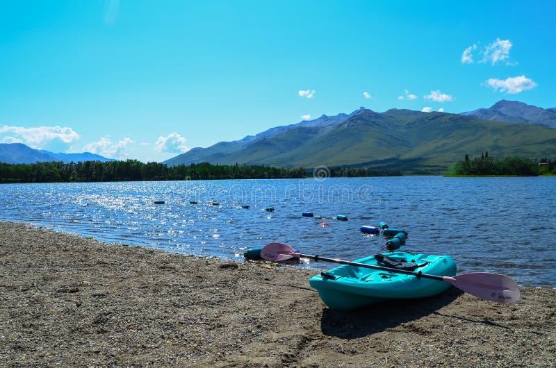 在Otto湖前面的蓝色皮船在有山的希利在上面背景和天空蔚蓝中 阿拉斯加,美国 免版税库存照片